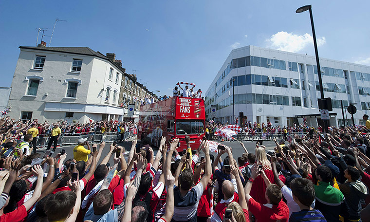 Arsenal players wave to fans from the bus
